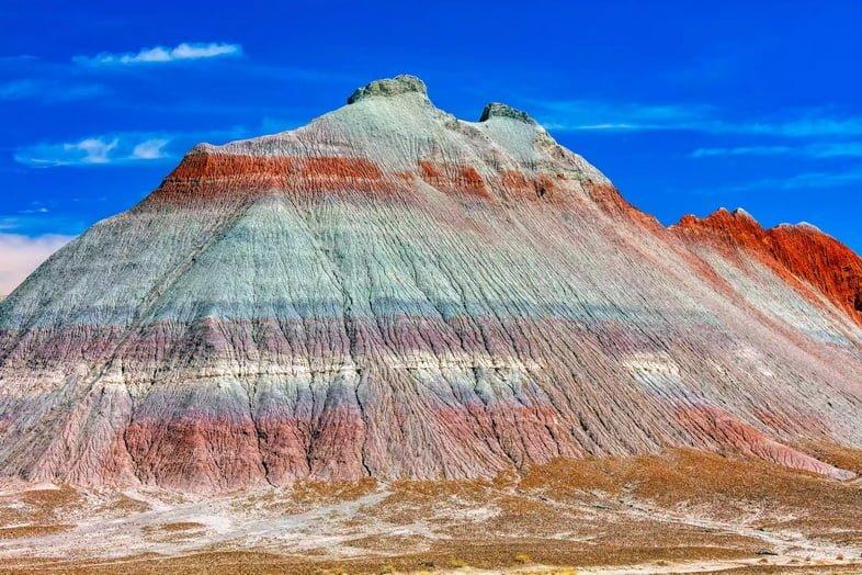 Гора в пустыне со слоями красного, серого, синего и фиолетового камня.