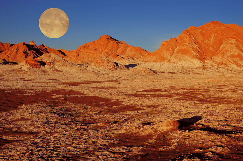 Полная луна на закате над яркими красными горами в пустыне Атакама, Чили