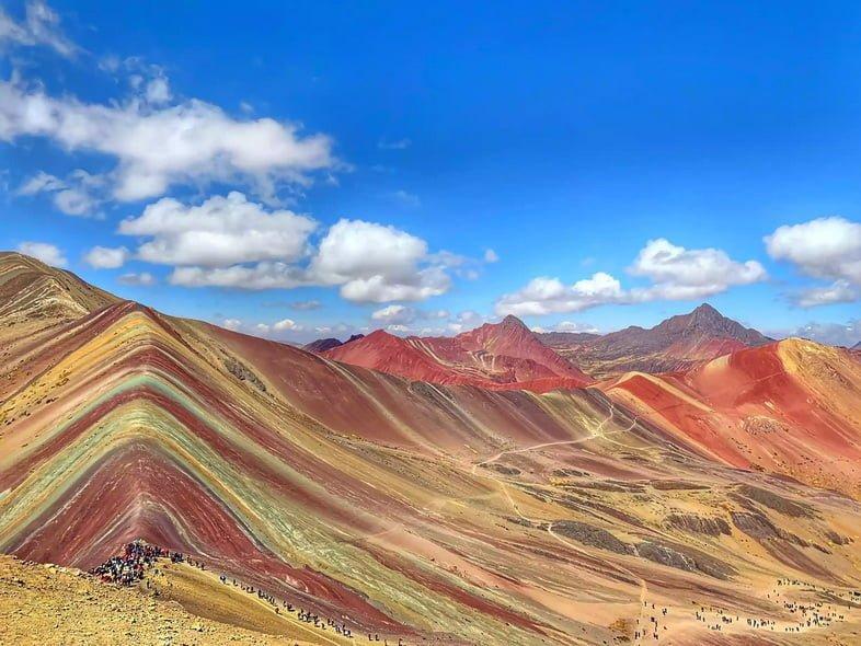 Разноцветный горный хребет в солнечный день с вереницей туристов на тропе
