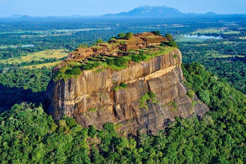 Каменный монолит среди лесов с древними руинами на вершине.
