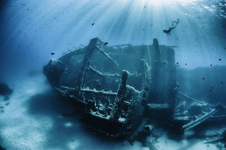 Небольшое затонувшее судно с ныряющим с поверхности ныряльщиком.