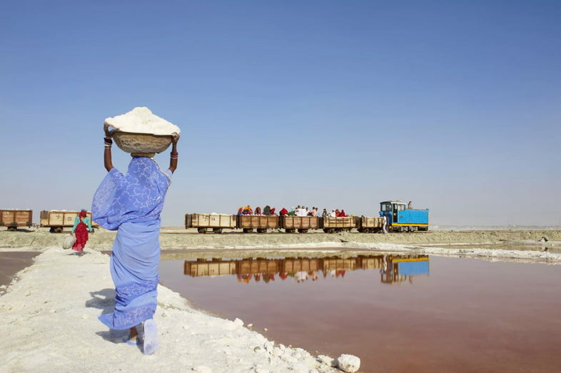 Женщина, несущая корзину с солью на берегу озера