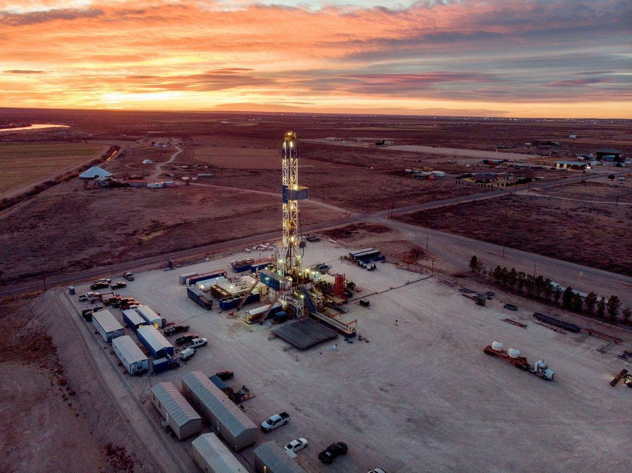 Вид с дрона на буровую установку для бурения нефтяных или газовых скважин на закате в Нью-Мексико